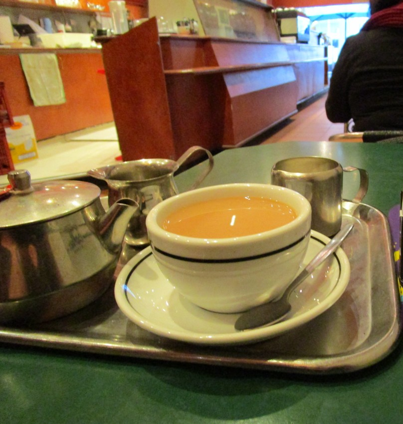 Photo of poured tea on a metal tray in a city coffee shop